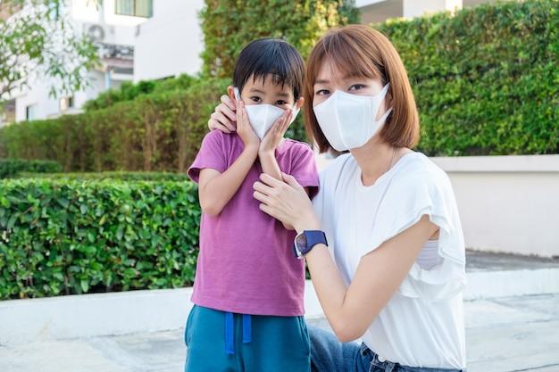 Asiática jovem mãe usando máscara de proteção pm2.5 para seu filho no parque ao ar livre