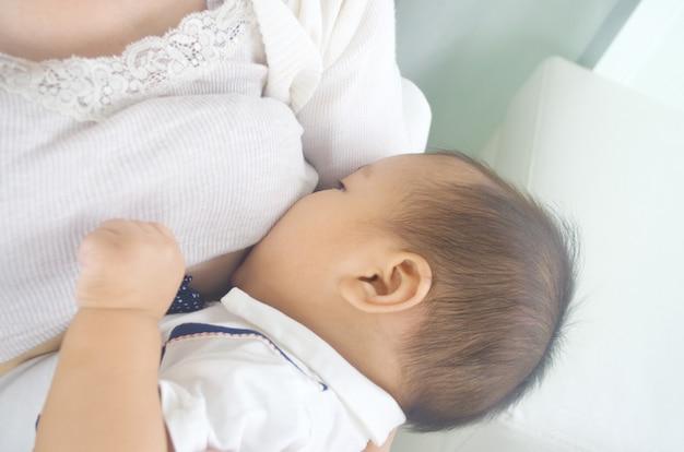 Asiática mãe amamentando seu bebê menino