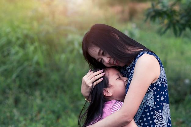 Asiática mãe e filha abraçando com amor no parque