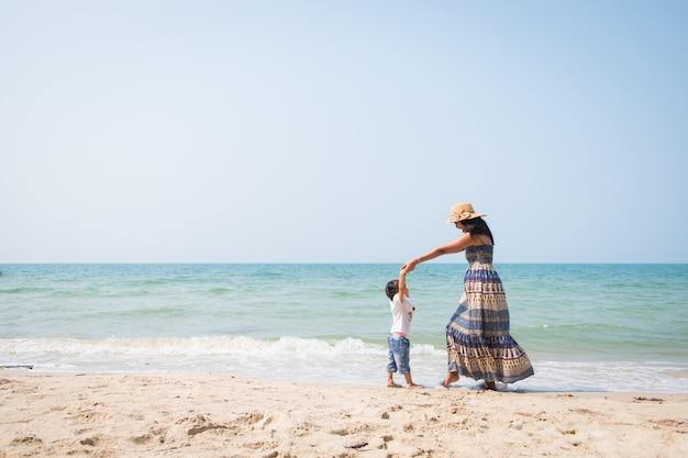 Asiática mãe e filha estão jogando dançando juntos na praia