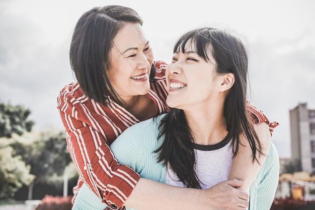 Asiática mãe e filha se divertindo ao ar livre - família feliz, aproveitando o tempo juntos em torno da cidade na ásia