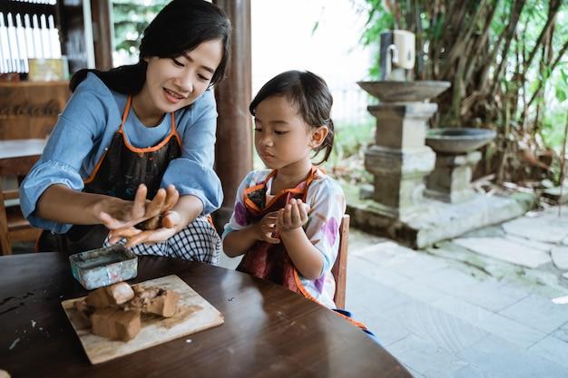Asiática mãe e filha trabalhando com argila
