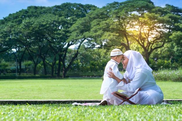 Asiática mãe muçulmana e seu filho sorrindo, abraçando e beijando juntos