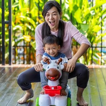 Asiática mãe solteira com filho estão brincando com o brinquedo do carro juntos quando vivendo em casa moderna