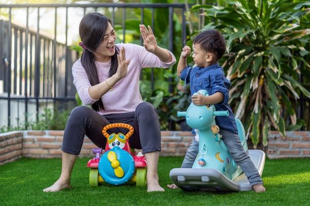 Asiática mãe solteira com filho estão brincando com o brinquedo juntos quando vivem no gramado da frente