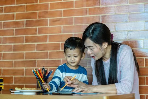Asiática mãe solteira com o filho estão desenhando juntos quando vivem em casa de loft para auto-aprendizagem