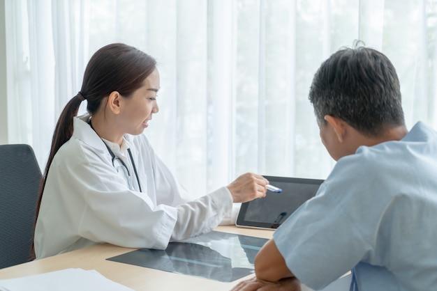 Asiática médica e paciente discutindo algo enquanto está sentado à mesa