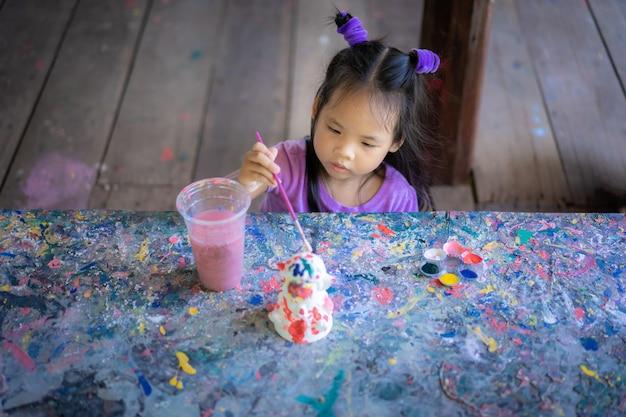 Asiática menina bonitinha se divertindo para pintar na boneca de estuque