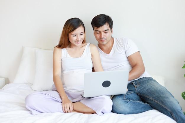 Asiática, mulher grávida, em, quarto, relaxante, com, dela, marido
