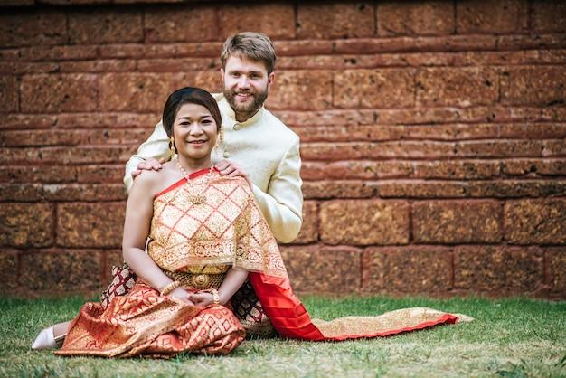 Asiática noiva e caucasiano noivo tem tempo romântico com vestido de tailândia