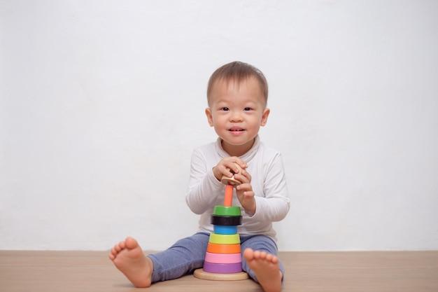 Asiática pequena bonito 18 meses / 1 ano de idade bebê criança brincadeira com brinquedo pirâmide de madeira colorida / brinquedo anel de empilhamento. criança brincando com brinquedo educacional isolado na parede branca, com espaço de cópia
