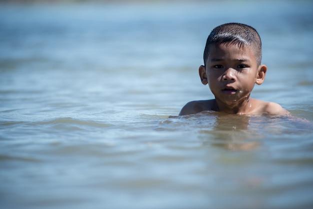 Asiática pequena criança brincar na água e fazendo respingo