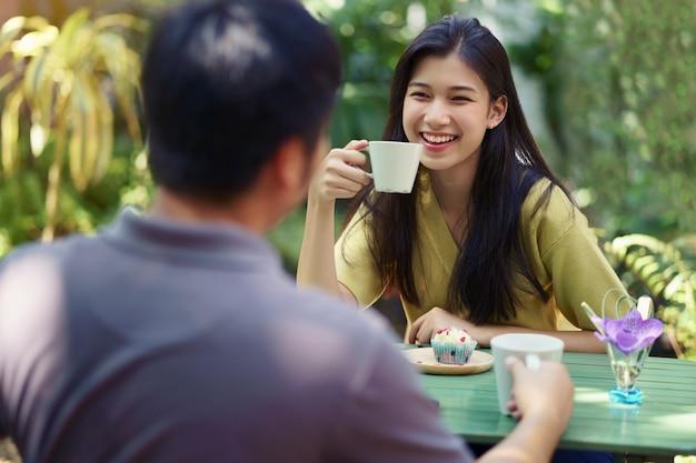 Asiática, sorrindo, par, desfrutando, date conversando, e, café bebendo, em, café ao ar livre