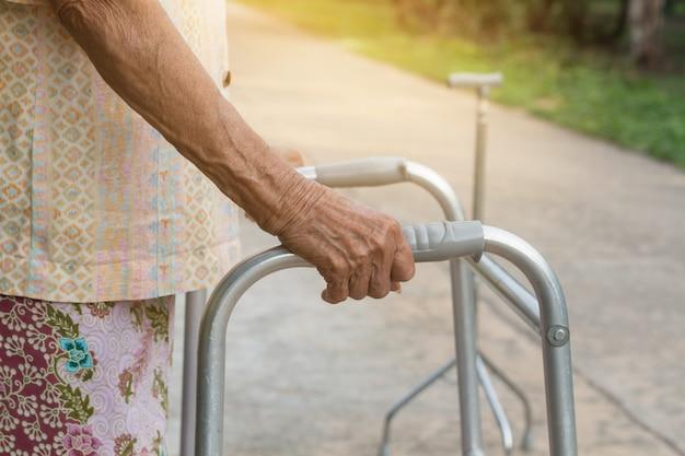 Asiática velha em pé com as mãos sobre uma bengala
