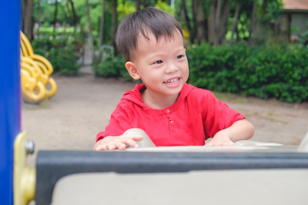 Asiático 3-4 anos de idade criança menino se divertindo subindo em pedregulhos artificiais no playground no parque