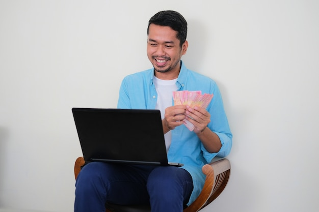 Asiático adulto mostrando expressão de felicidade enquanto conta o dinheiro que ganha