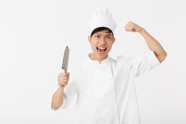 Asiático animado chefe com uniforme branco de cozinheiro, sorrindo para a câmera enquanto segura uma grande faca isolada sobre a parede branca