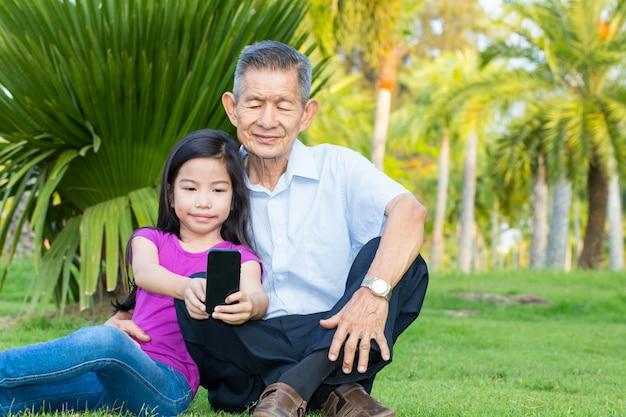 Asiático, avô, e, neto, levando, selfie, com, smartphone, parque