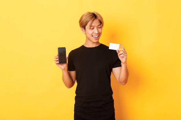 Asiático bonito e satisfeito segurando um cartão de crédito e mostrando a tela do smartphone