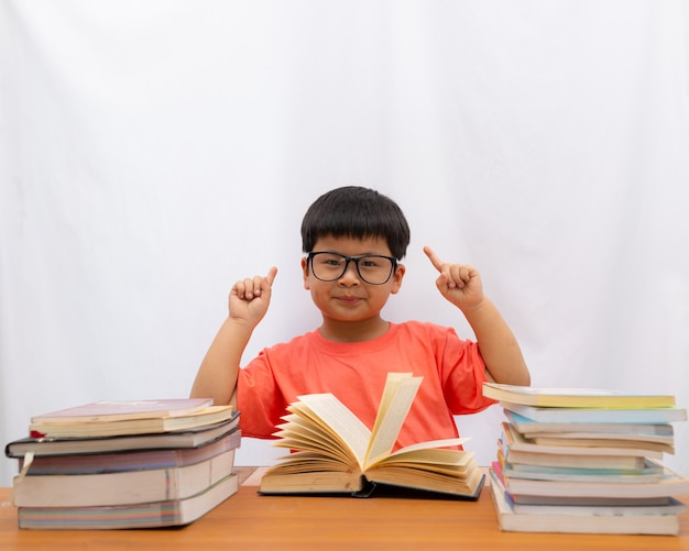 Asiático bonito um menino lendo com o dedo segurando sobre fundo branco,