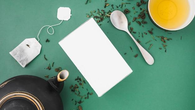 Asiático bule, saquinho de chá, colher e chá de ervas em pano de fundo colorido