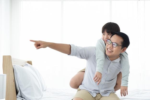 Asiático carrega o filho na cama, família feliz em casa.