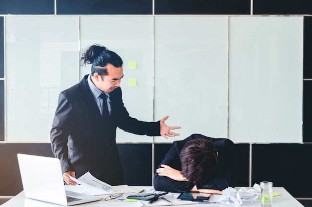 Asiático chefe irritado e irritado gritando no homem de negócios triste reprimenda empregada deprimida