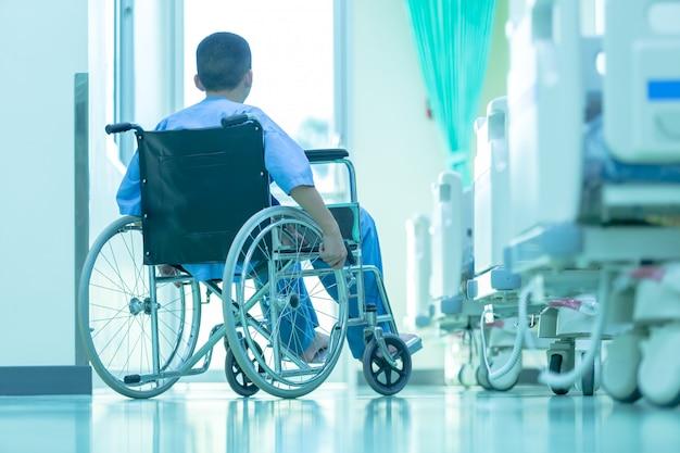 Asiático com deficiência homem está sentado em uma cadeira de rodas. ele segura as mãos no volante, medical eq