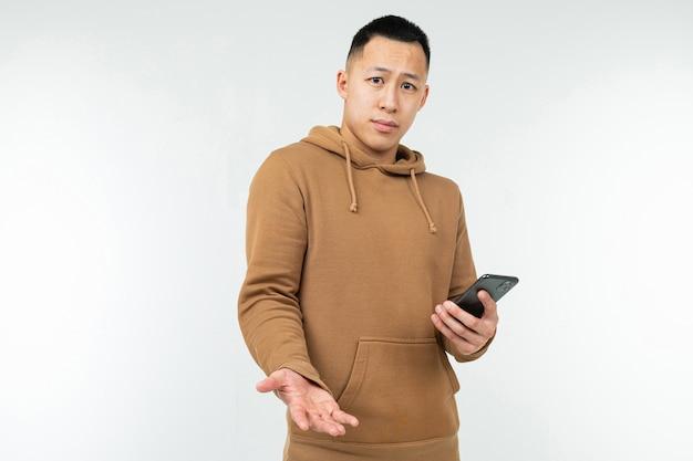 Asiático considerável no hoodie ocasional com um telefone em suas mãos em um fundo branco com espaço da cópia