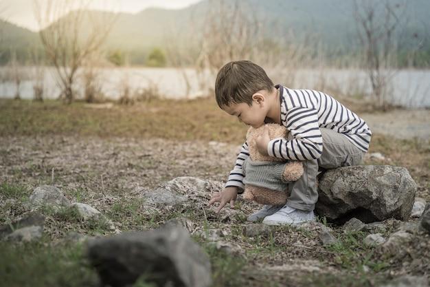 Asiático da criança com o local de assento do urso de peluche o reservatório é o fundo.