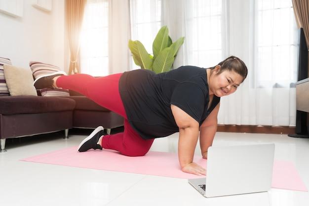 Asiático de mulher gorda se exercitando e está usando um computador laptop em casa, o conceito de ideia de esporte e recreação.