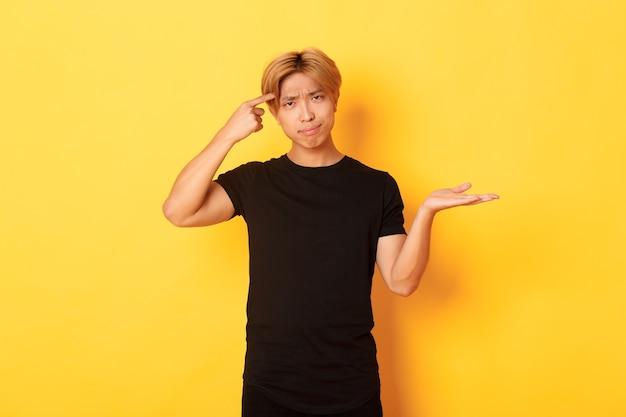 Asiático decepcionado com cabelo loiro, levantando a mão intrigado e repreendendo alguém que agia de estúpido, parado na parede amarela
