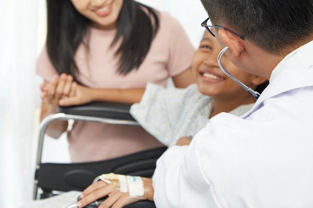 Asiático, doutor masculino, falando, para, criança jovem, cadeira rodas, e, mãe, conceito, cuidado hospital