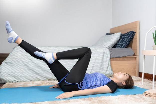 Asiático fazendo exercícios em casa e fazendo ioga em um colchonete