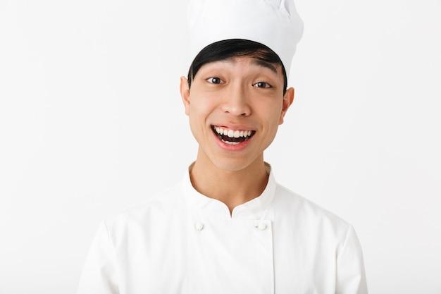 Asiático feliz chefe homem com uniforme de cozinheiro branco, sorrindo para a câmera em pé, isolado sobre uma parede branca