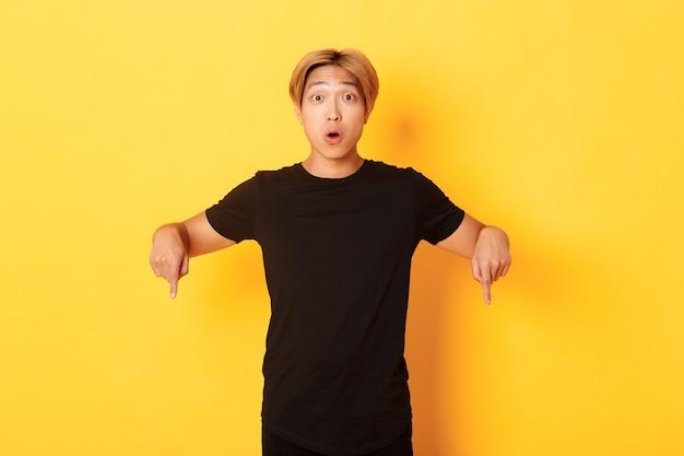 Asiático feliz divertido, apontando os dedos para baixo e ofegando, impressionado, mostrando um anúncio incrível, parede amarela.