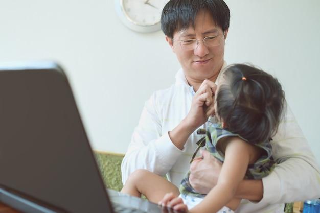 Asiático feliz e sorridente empresário brincando com sua filha enquanto trabalhava em casa, pai e filha passando um tempo juntos