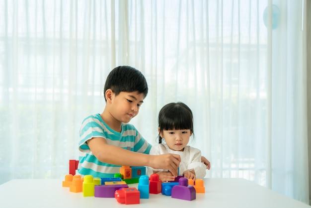 Asiático fofo irmão e irmã brincando com brinquedos