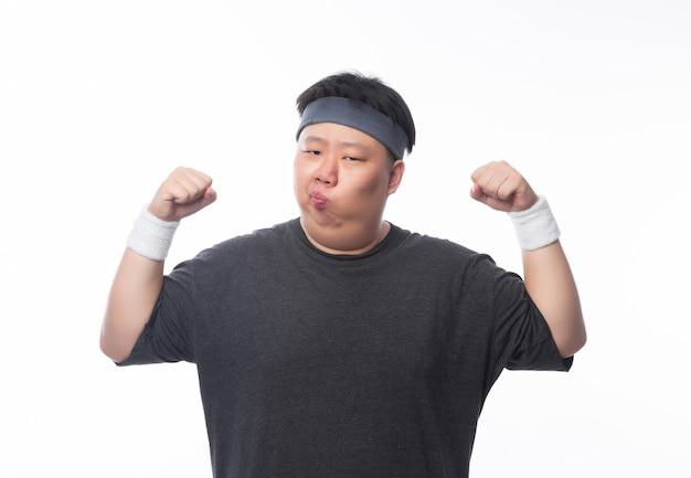Asiático gordo engraçado em roupas de esporte, mostrando a força e olhando para copyspace isolado no fundo branco