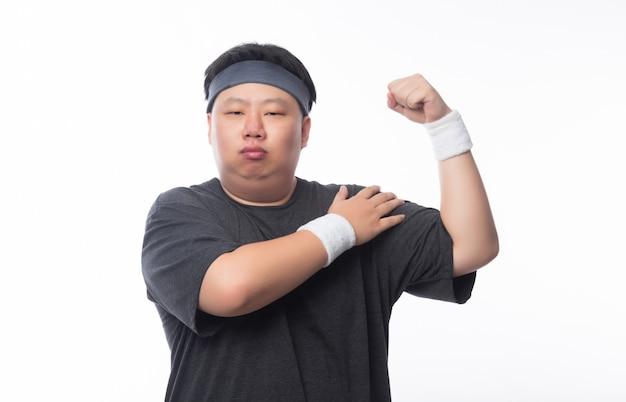 Asiático gordo engraçado em roupas de esporte, mostrando a força