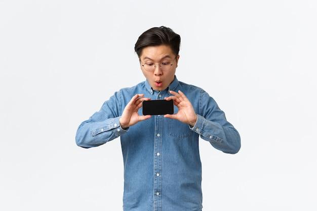 Asiático impressionado reagindo ao trailer do novo filme, mostrando a tela do celular de amigos, olhar impressionado