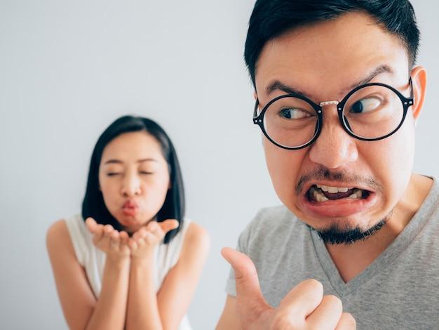 Asiático irritado e irritado marido com esposa feliz e teimosa