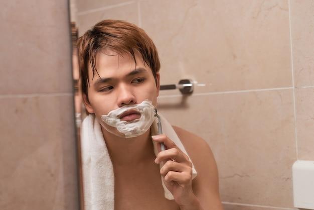Asiático jovem bonito está barbeando o rosto e olhando no espelho.