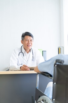 Asiático médico e paciente estão discutindo