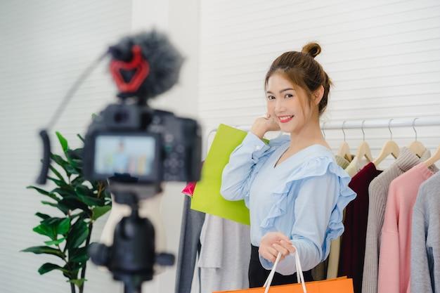 Asiático moda feminina blogger on-line influenciador segurando sacolas de compras e muitas roupas