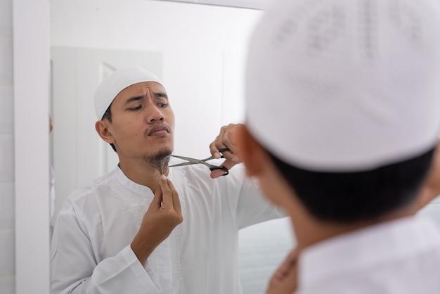 Asiático muçulmano que não tem certeza de raspar a barba com uma tesoura