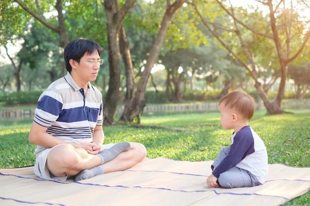 Asiático pai com os olhos fechados e criança de menino de 1 ano de idade criança pratica ioga & meditando ao ar livre na natureza no verão, conceito de estilo de vida saudável