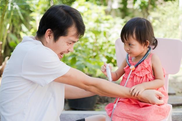 Asiático pai e filha fazendo papel de médico e paciente,