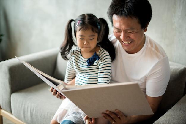 Asiático pai e filha lendo juntos