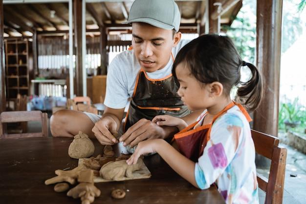 Asiático pai e filha trabalhando com argila
